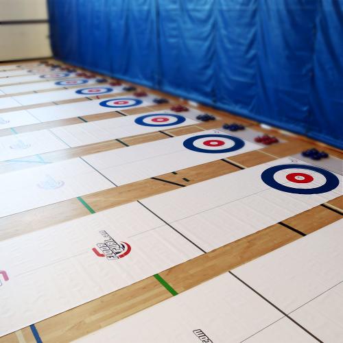 Several full rink FloorCurl mats set up side by side in a school gym.
