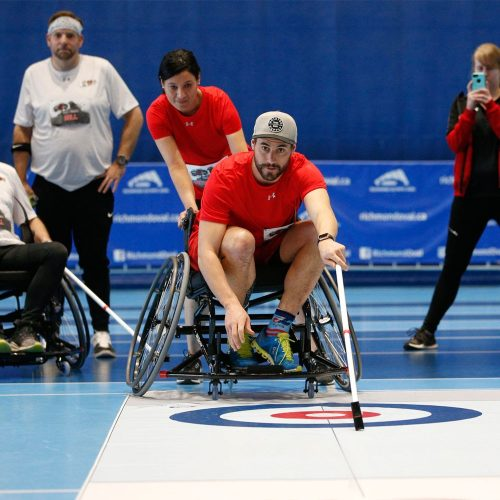 An athletic man in a wheelchair is using a FloorCurl pusher stick to deliver a FloorCurl stone in a game, while teammates and friends watch and cheer.
